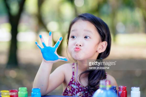 happy little child painting water color with her hand. smiley little child girl with painted hand. - human body part stock pictures, royalty-free photos & images