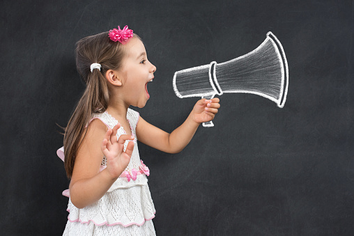 Happy Little Child Schoolgirl Makes Announcement Call for Back To School 991060890