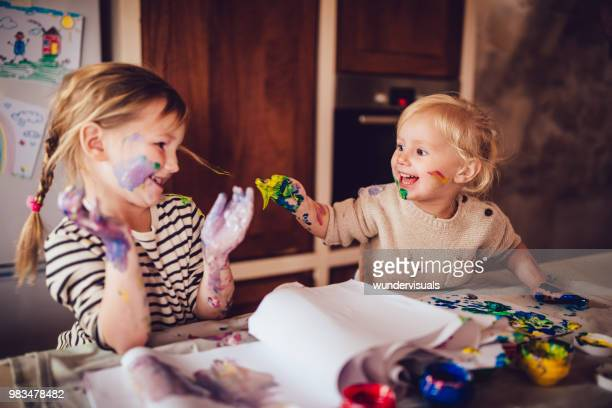 Happy little children having fun finger painting at home