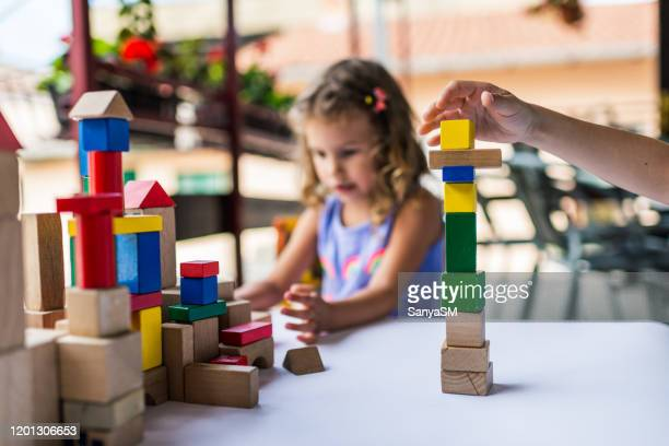 happy little children playing with colorful building blocks - montessori education stock pictures, royalty-free photos & images