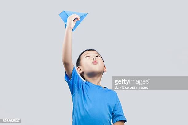 Happy little Chinese boy throwing a paper airplane
