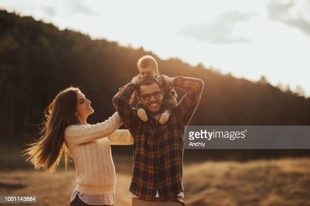 Happy little family enjoying autumn day in forest