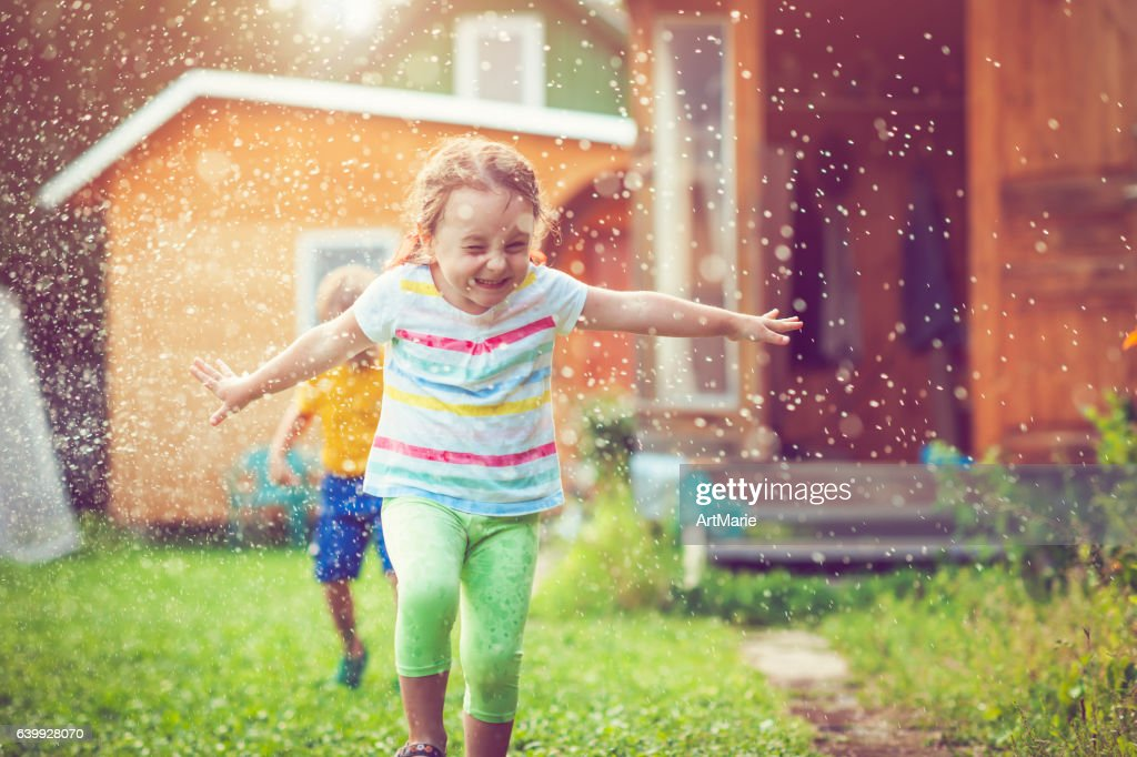 Happy little girl and boy playing with garden sprinkler : Stock Photo