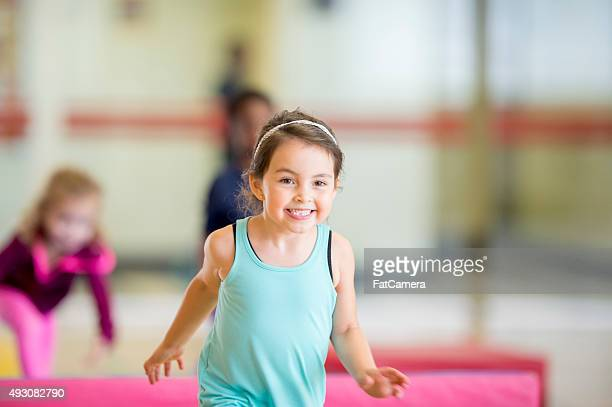 happy little girl at gymnastics - gymnastiek stockfoto's en -beelden