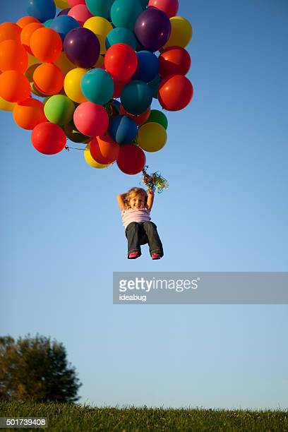 Happy Little Girl Being Carried Away by Helium Balloons