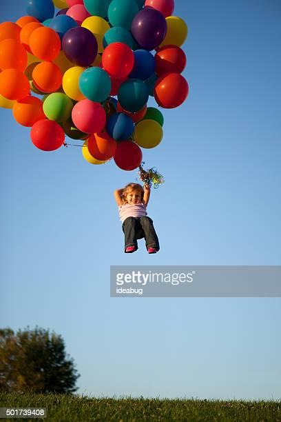 Fillette heureuse d'être transporté par l'hélium ballons