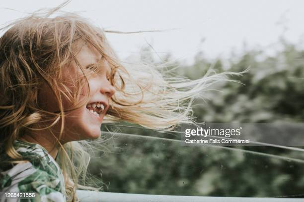 happy little girl beside an open car window as her hair blows in the wind - freedom stock pictures, royalty-free photos & images