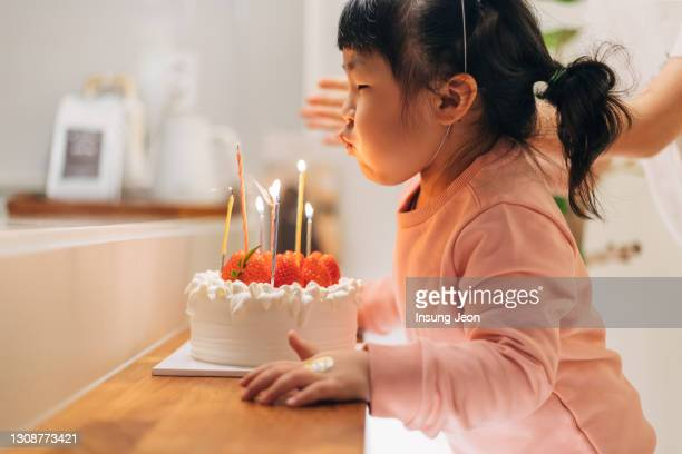 happy little girl blowing out the candles on her birthday cake - candle stock pictures, royalty-free photos & images