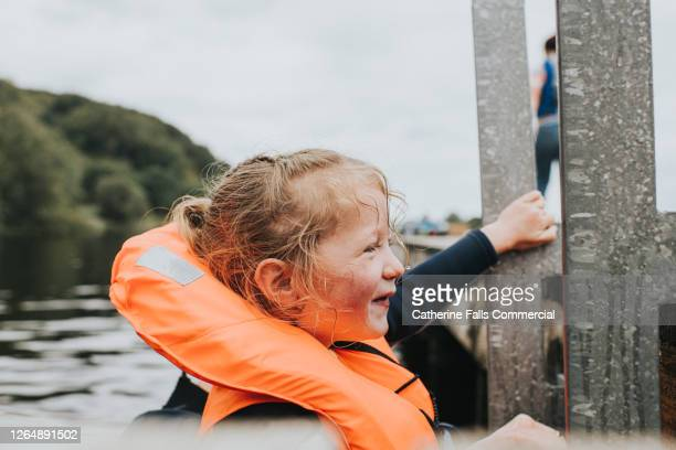 happy little girl climbing up a ladder onto a jetty wearing a bright orange lifejacket - mountaineering stock pictures, royalty-free photos & images