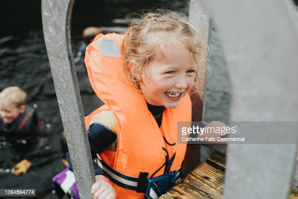 happy little girl climbing up a ladder onto a jetty wearing a bright orange lifejacket - lake stock pictures, royalty-free photos & images