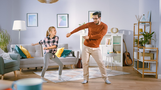 Happy Little Girl Dances with Young Father in the Middle of the Living Room. Happy Family Time, Father and Daughter Dancing at Home. 1161176817