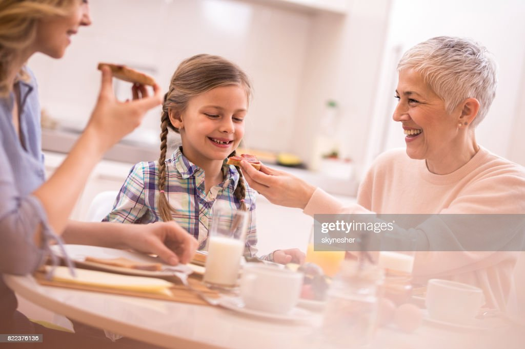 Happy little girl enjoying in breakfast time with her grandmother and mother. : Stock Photo
