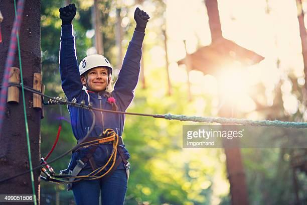 Niña feliz disfrutando de campo de cuerdas parque de aventuras