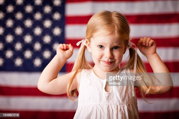 Happy Little Girl Flexing in Front of American Flag