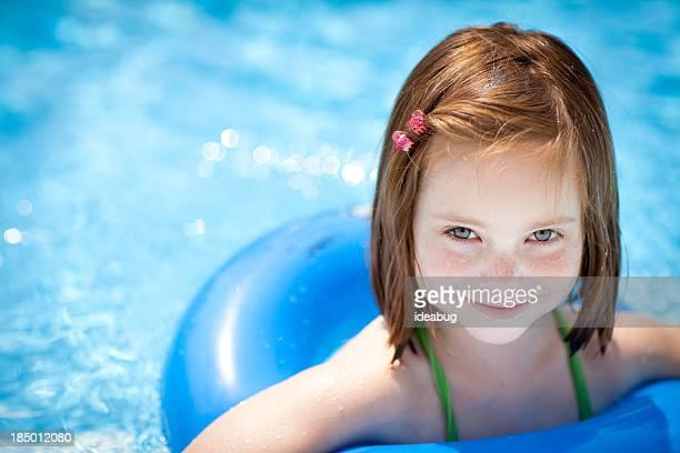 Glückliches kleines Mädchen mit Wasser schwimmen Ring im Swimmingpool