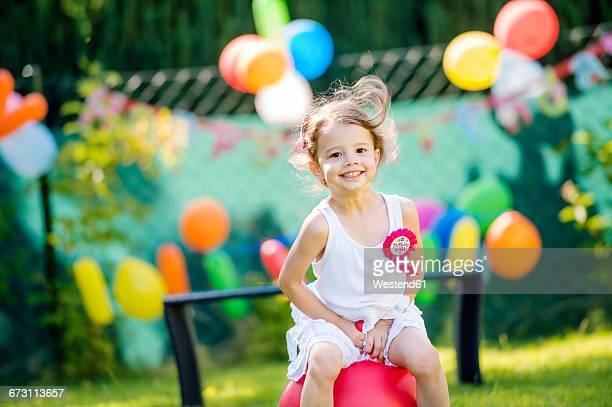 Happy little girl having birthday party in the garden