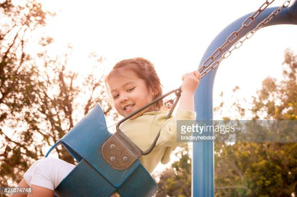 Happy little girl having fun on swing at playground