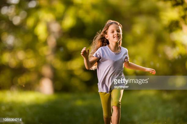 Happy little girl having fun while running in nature.