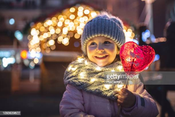 happy little girl holding a lolipop and enjoying christmas holidays - happy holidays stock photos and pictures