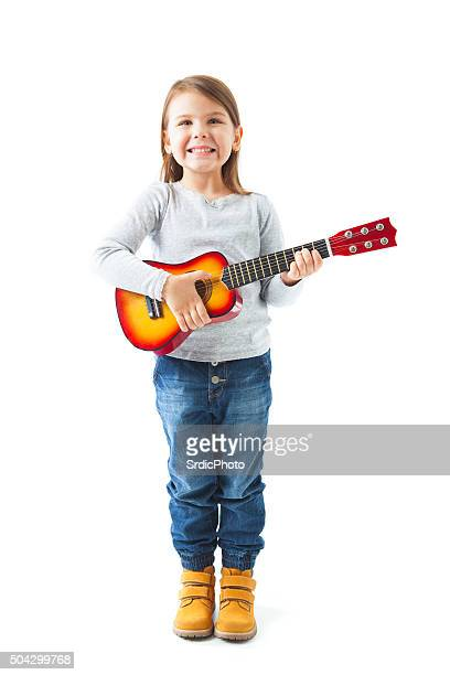 Happy little girl holding acoustic guitar