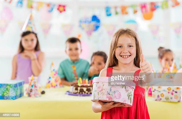 Happy little girl holding birthday presents and showing thumb up.