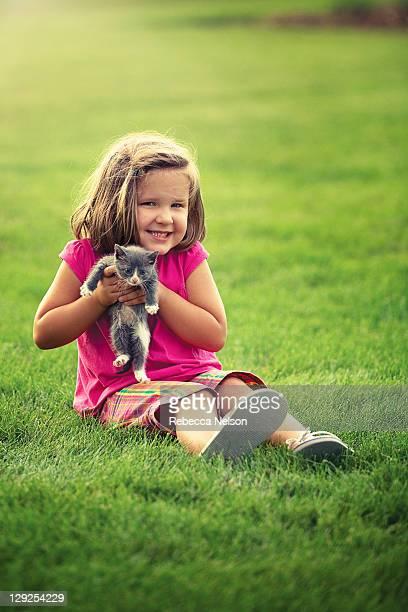 Happy little girl holding gray kitten