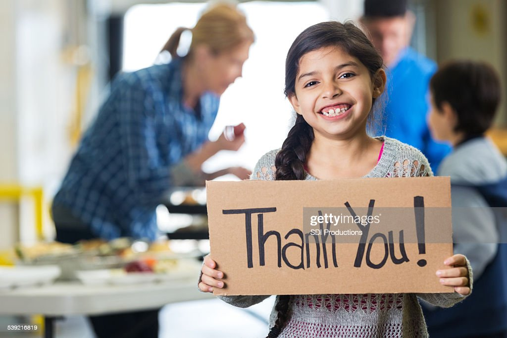Happy little girl holding THANK YOU sign in food bank : Stock Photo