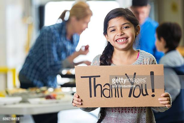 Happy little girl holding THANK YOU sign in food bank