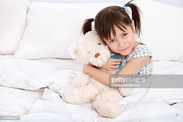 Happy little girl hugging teddy bear in bed
