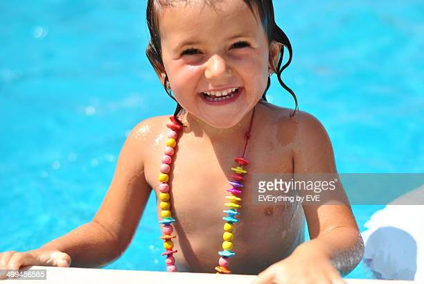 Happy little girl in a pool on the beach
