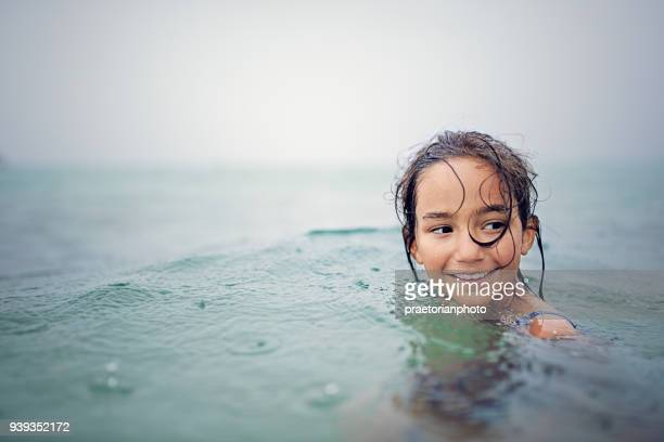 happy, little girl is swimming in the ocean in a rainy day - bottomless girls stock pictures, royalty-free photos & images