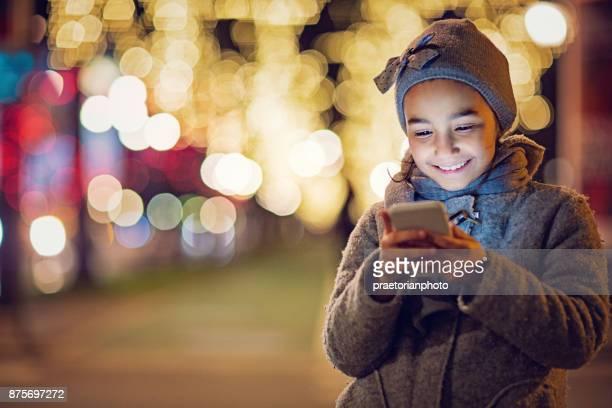 Gelukkig, het meisje is SMS op de versierde straat met Kerstmis