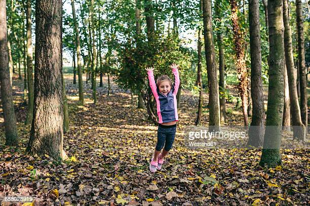 Happy little girl jumping in the air in the woods