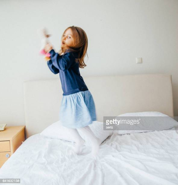 Happy little girl jumping on bed