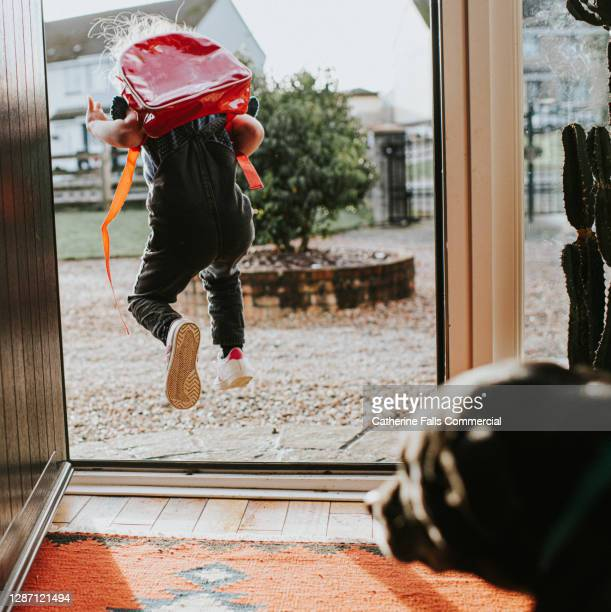 happy little girl leaps out the sunny front door, while wearing a red backpack. her dog looks on as she leaves. - preschool child stock pictures, royalty-free photos & images