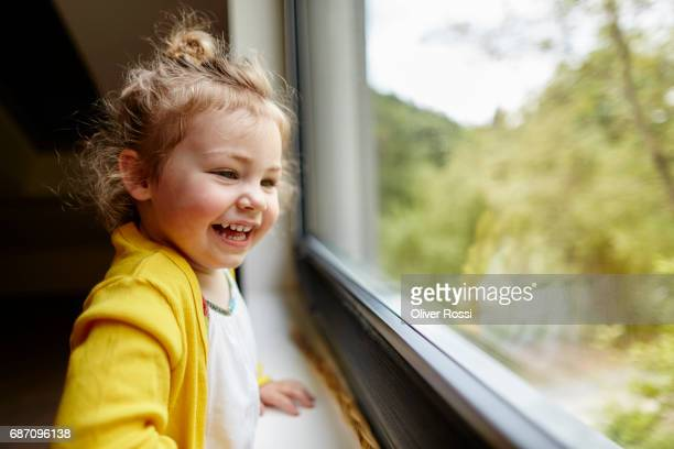 Happy little girl looking out of the window