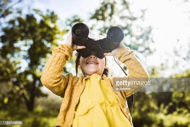 happy little girl looking through binoculars in nature. - binoculars stock pictures, royalty-free photos & images