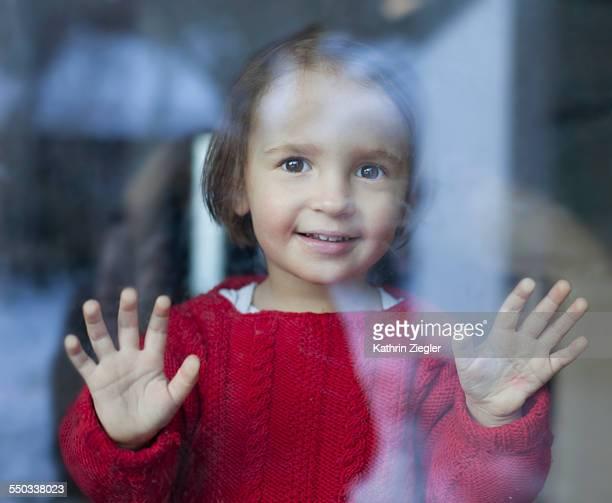 happy little girl looking through window
