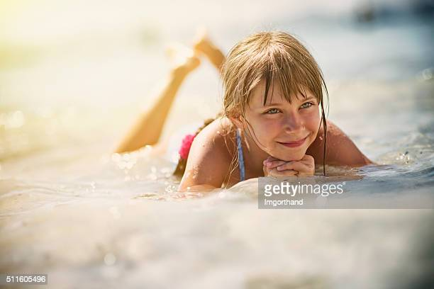 Happy little girl lying in sea on a beach.