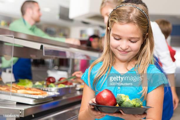 Glückliches kleines Mädchen machen gesunde Speisen in der cafeteria der Schule