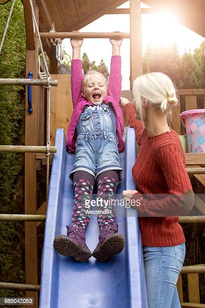 happy little girl on a slide watching her mother - bambini in mutande foto e immagini stock