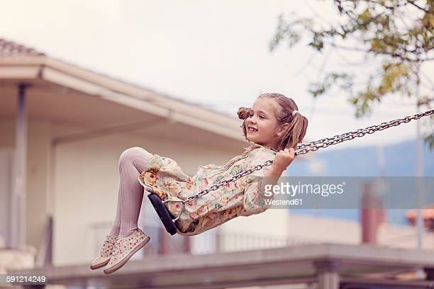 Happy little girl on a swing