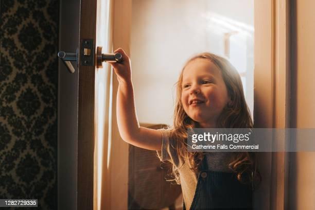 happy little girl opens an interior door and peeks around into a dark room - door stock pictures, royalty-free photos & images