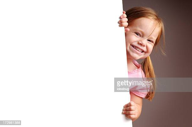 happy little girl peeking from behind blank sign - blank sign stock photos and pictures