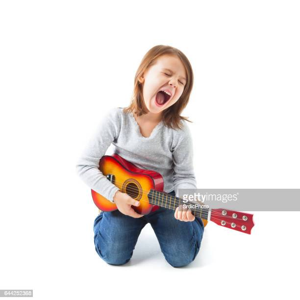 Happy little girl playing acoustic guitar