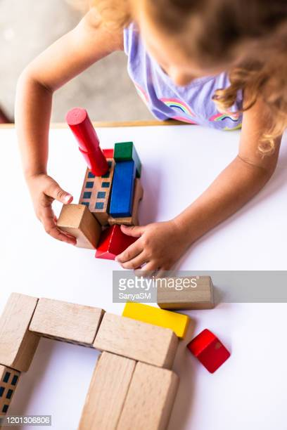 happy little girl playing with colorful building blocks - montessori education stock pictures, royalty-free photos & images