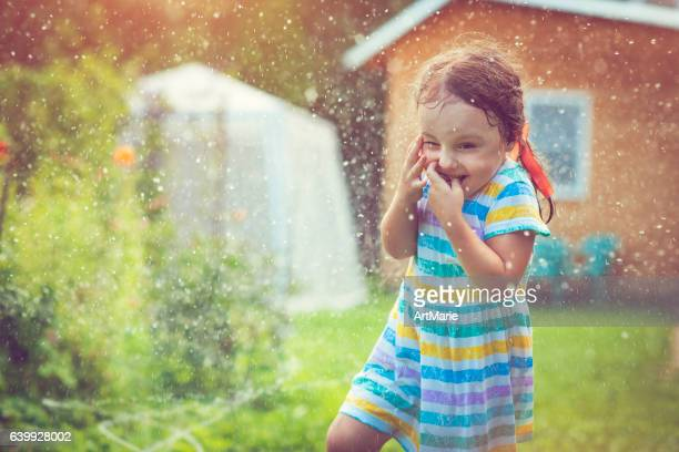 Happy little girl playing with garden sprinkler