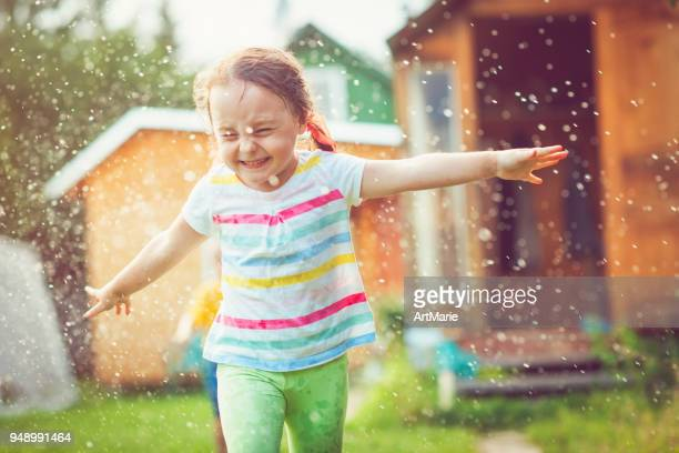 happy little girl playing with garden sprinkler - playing stock pictures, royalty-free photos & images