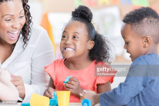 happy little girl playing with modeling clay - clay stock pictures, royalty-free photos & images