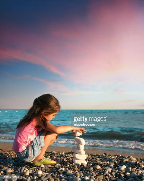 happy little girl playing with stones on beach - girl mound stock pictures, royalty-free photos & images